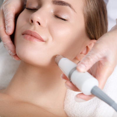 Calm young woman getting cavitation rejuvenation skin treatment